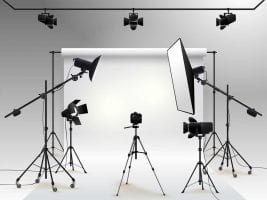 Photography studio with lights and cameras pointing at a white backdrop