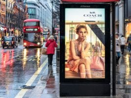An outdoor bus shelter advertisement on a pavement in London